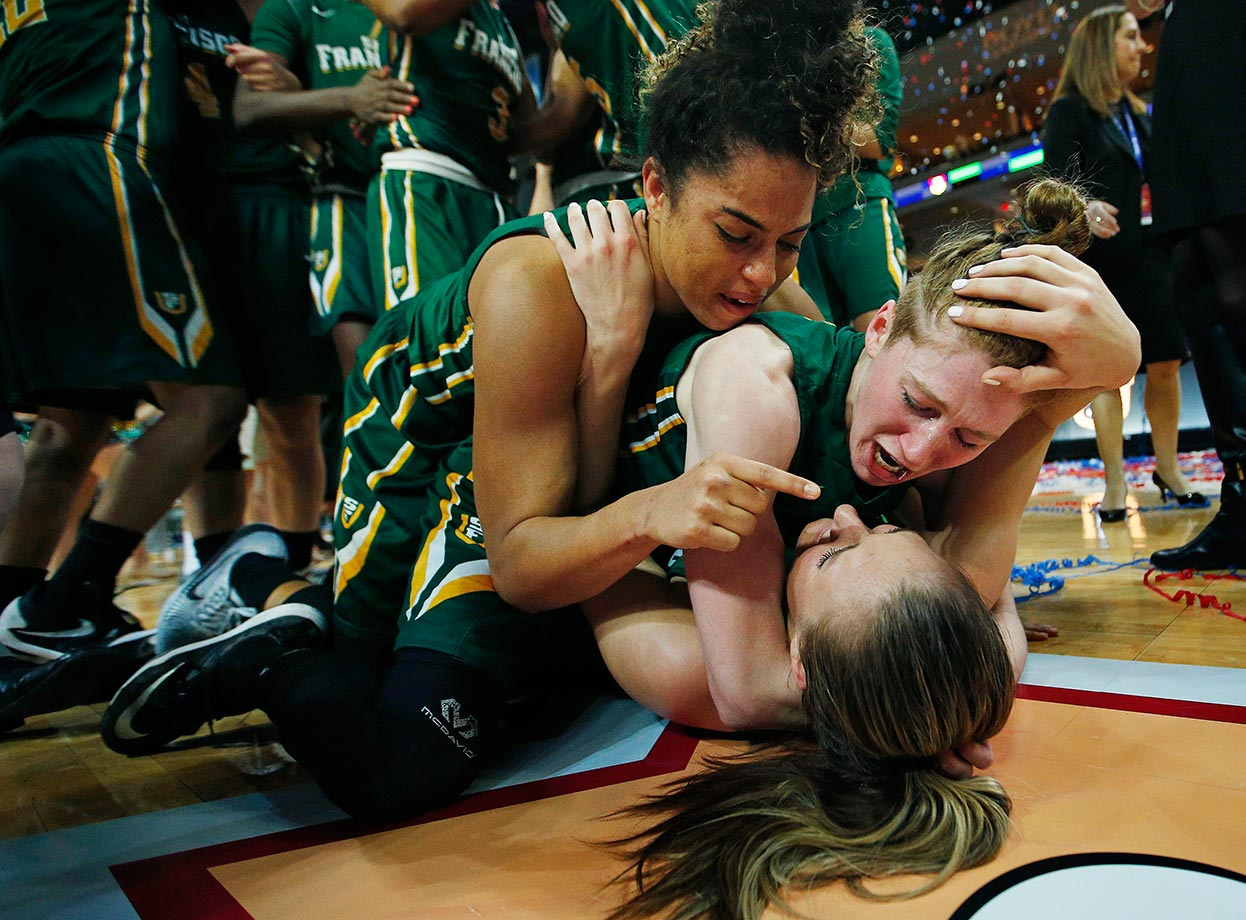 San Francisco's Zhane Dikes and Rachel Howard pounce on teammate Taylor Proctor after they defeated BYU in a West Coast Conference tournament game in Las Vegas.