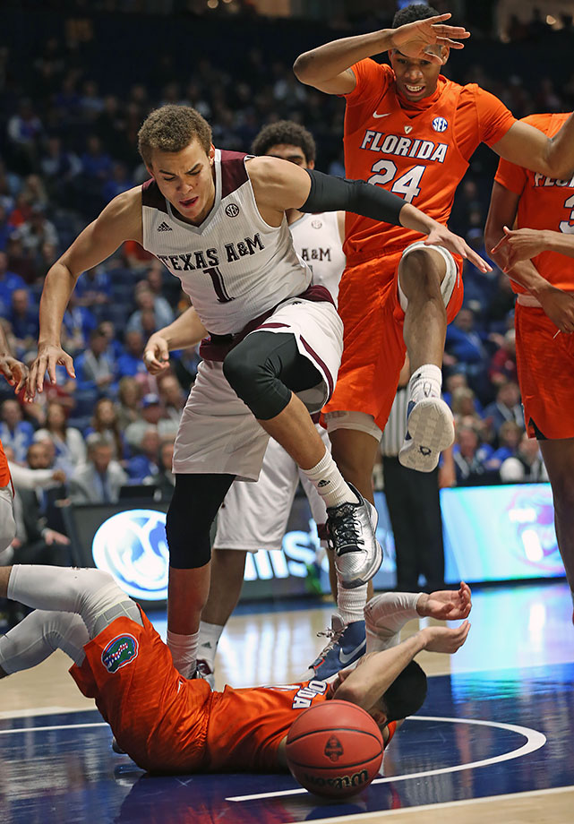 Texas A&M forward DJ Hogg and Florida forward Justin Leon chase a loose ball over Florida guard Chris Chiozza during the first half of their SEC Tournament game in Nashville.