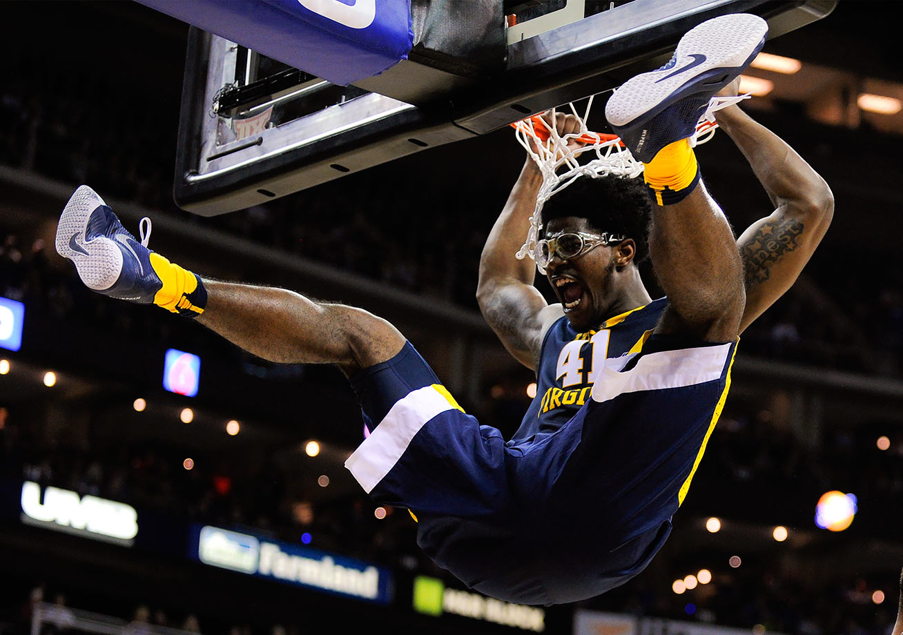 West Virginia forward Devin Williams hangs on the rim after dunking against Kansas in the first half of their Big 12 Basketball Tournament game in Kansas City.
