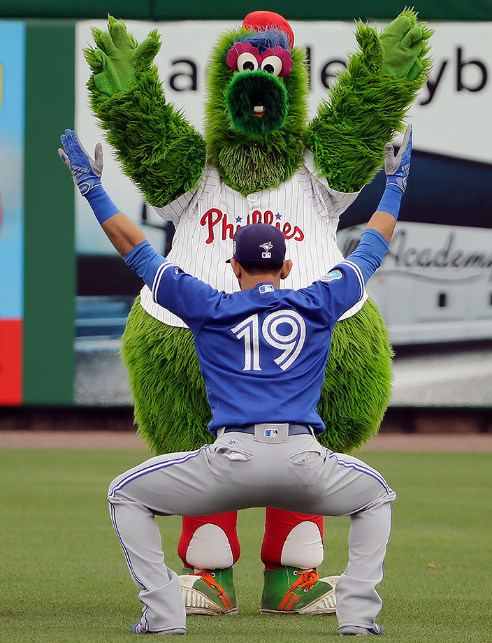 Philadelphia Phillies mascot The Philly Phanatic imitates Toronto Blue Jays outfielder Jose Bautista while he stretches in the outfield before a spring training game in Clearwater, Fla.