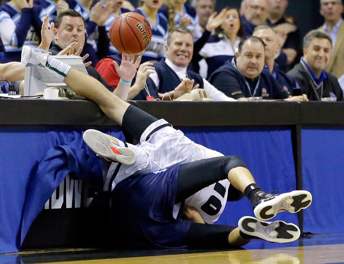 Barstow guard Tripp Walsworth and Father Tolton Catholic guard Michael Porter, Jr. fall into a courtside table while chasing a ball headed out of bounds during the first half of their Missouri Class 3 boys high school championship basketball game in Columbia, Mo.