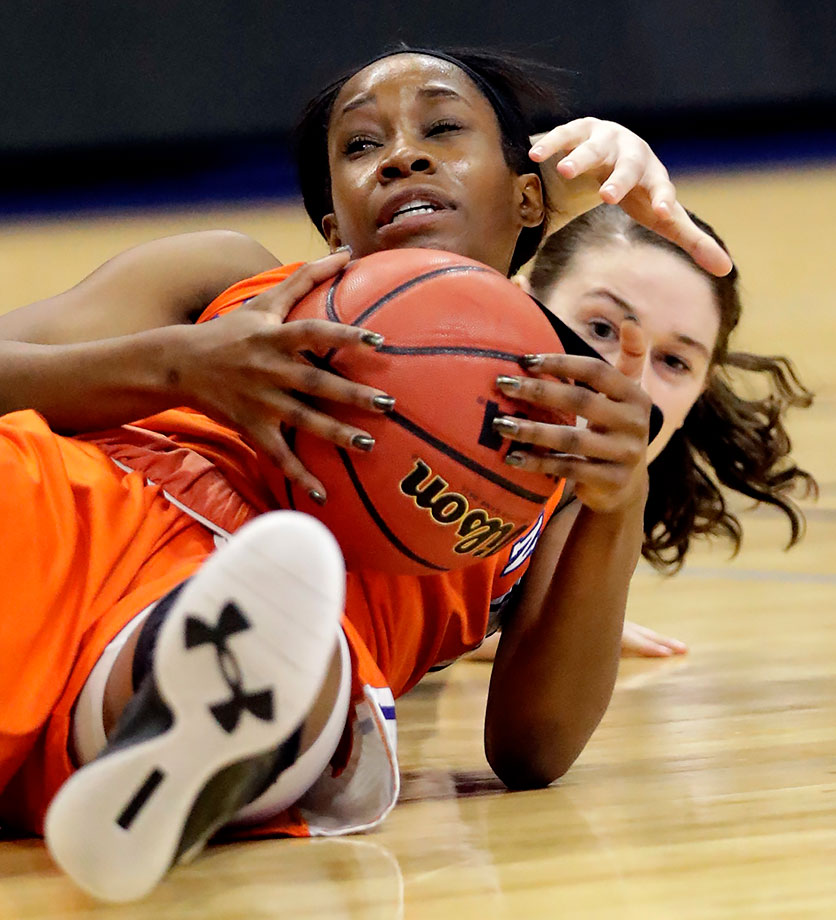 Sam Houston State guard Kamry Orr grabs the ball on the floor in front of Central Arkansas forward Taylor Baudoin during the first half of their Southland Conference Tournament game in Katy, Texas.