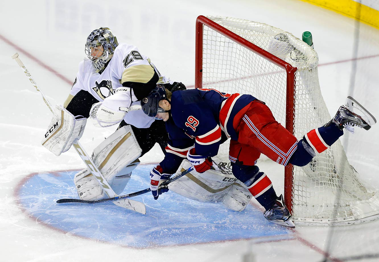 New York Rangers right wing Jesper Fast collides with Pittsburgh Penguins goalie Marc-Andre Fleury in the third period of their game in New York City.