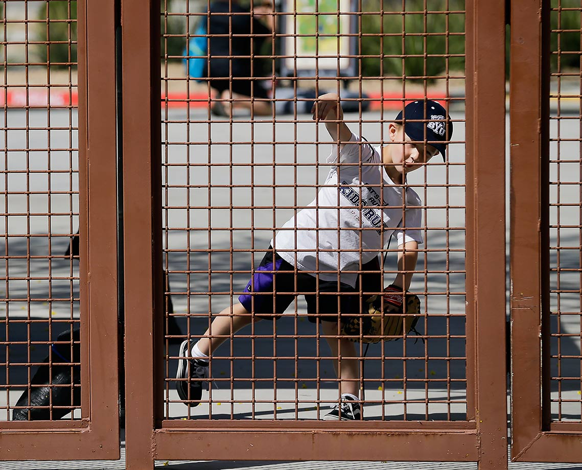 Four-year-old Porter Udall motions to throw while waiting for the gate to open to watch a spring training game between the Chicago White Sox and Los Angeles Dodgers in Phoenix, Ariz.