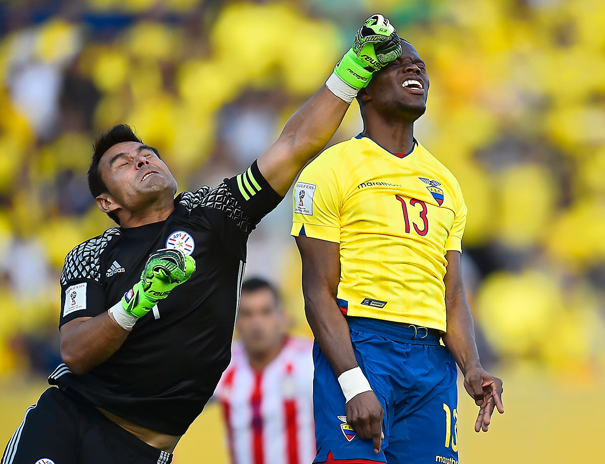 Paraguay's goalkeeper Justo Villar  clears the ball next to Ecuador's Enner Valencia during their 2018 FIFA World Cup Russia Qualifiers match in Quito, Ecuador.