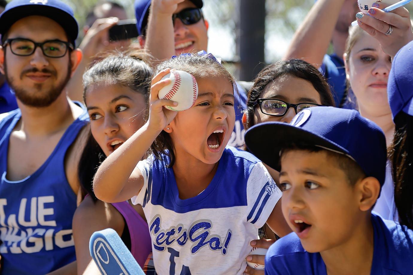 Fans ask for autographs as Los Angeles Dodgers players arrive for practice before the team's spring training game against the Cincinnati Reds in Phoenix.