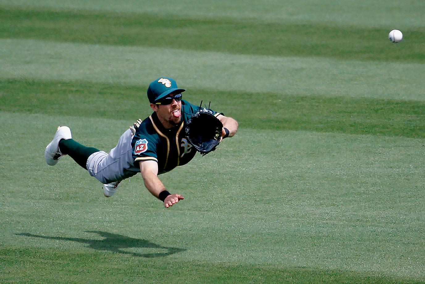 Oakland Athletics outfielder Billy Burns can't make the catch on a base hit during the second inning of a spring training game against the Chicago Cubs in Mesa, Ariz.
