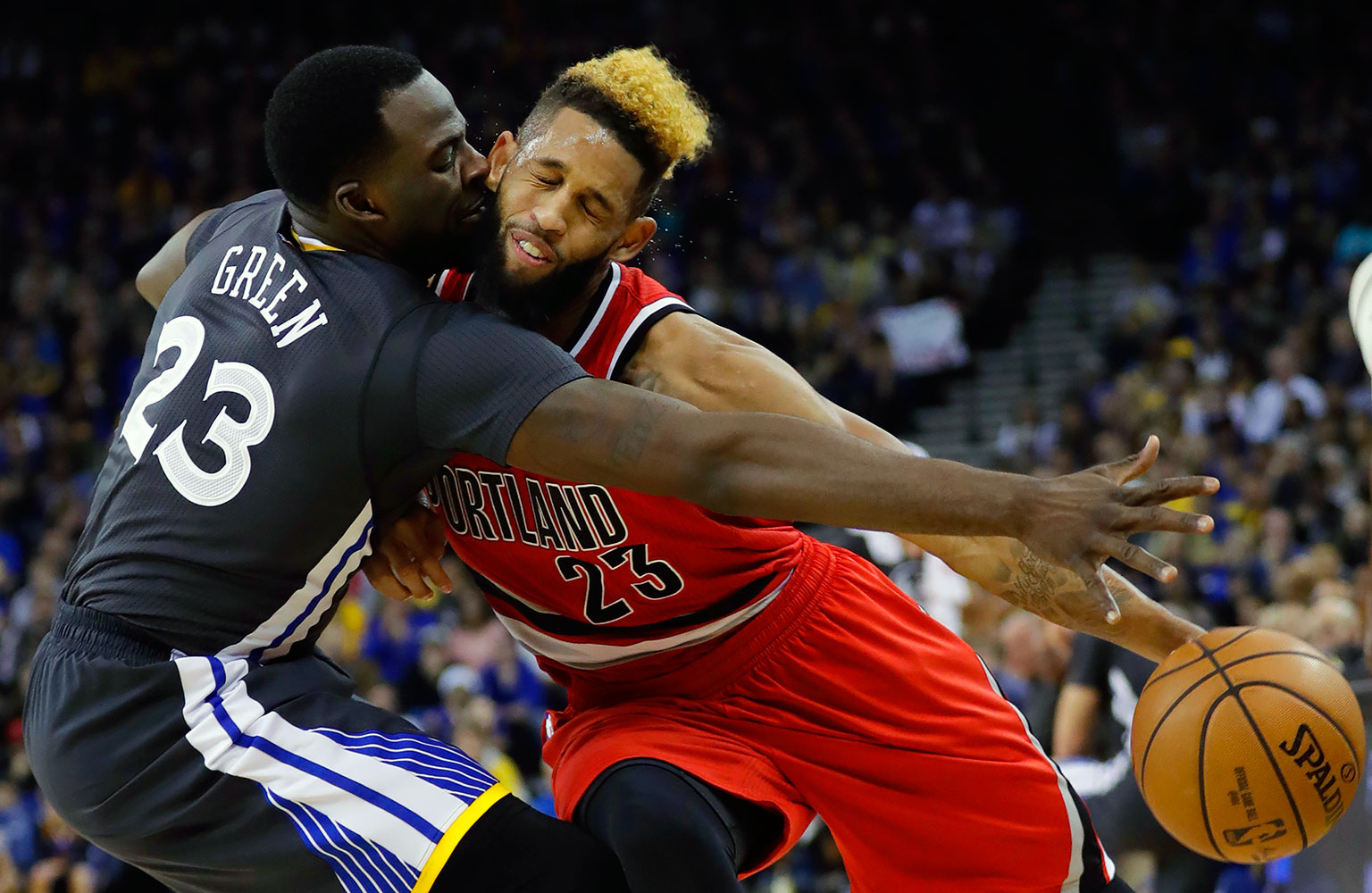 Golden State Warriors power forward Draymond Green fouls Portland Trail Blazers shooting guard Allen Crabbe on Dec. 17, 2016 at ORACLE Arena in Oakland, Calif.