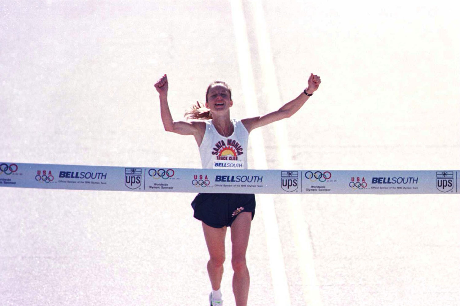 Jenny Spangler raises her hands in celebration just before crossing the finish line to win the 1996 Women's Olympic Marathon Time Trials held in Columbia, South Carolina.