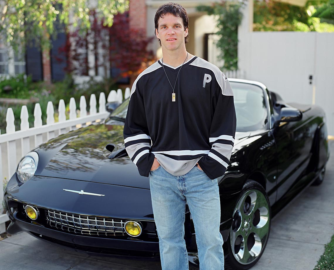 NHL All-Star Luc Robitaille posing by his Ford Thunderbird.