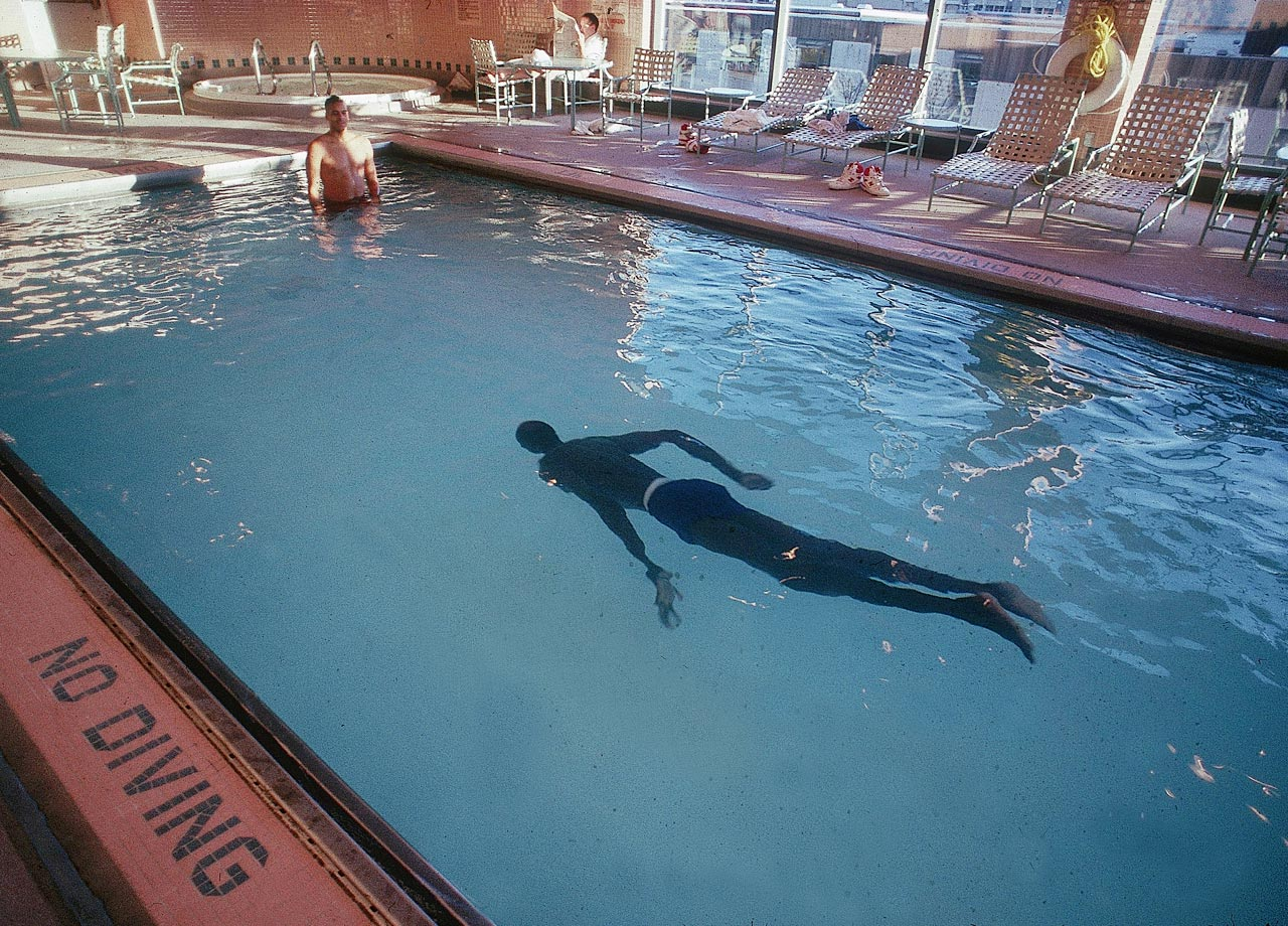 Every end is the shallow end for Manute Bol. In this photo, the 7-foot-7 basketball star glides eerily along the bottom of a swimming pool.