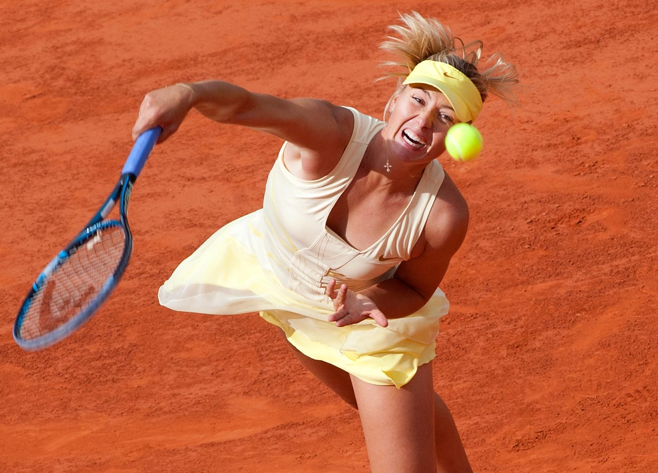 With the trademark red clay of the French Open underneath her, Sharapova smashes a powerful serve in 2011.