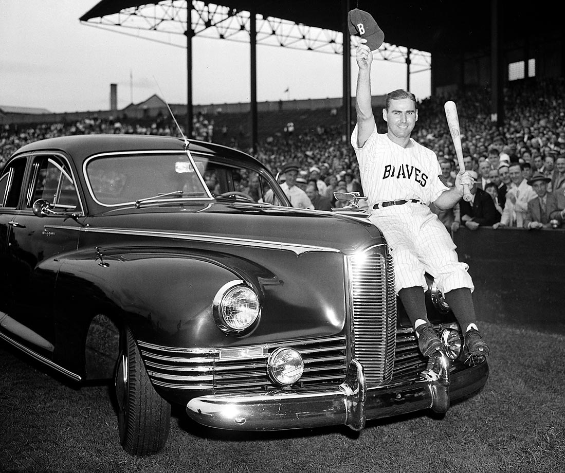 "Boston Braves outfielder Tommy Holmes waving his cap from the hood of this car awarded to him in 1945.  The vehicle was given on ""Tommy Holmes Day,"" in which the team and its fans celebrated the Major League's leading hitter."
