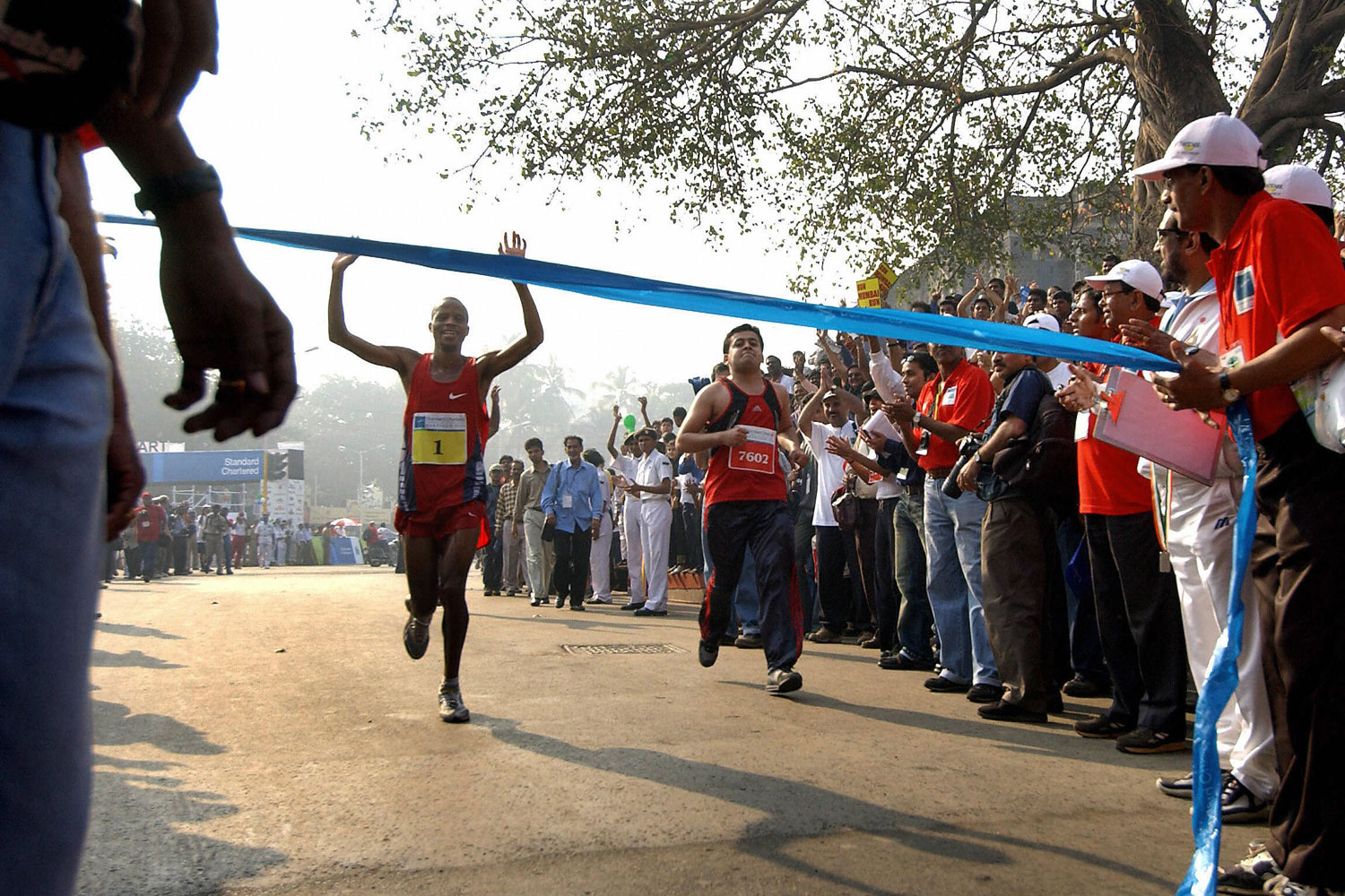 South African marathon runner, Hendrik Ramaala holds his hands in the air as he prepares to cross the finish line to win the 42.2km Bombay International Marathon.