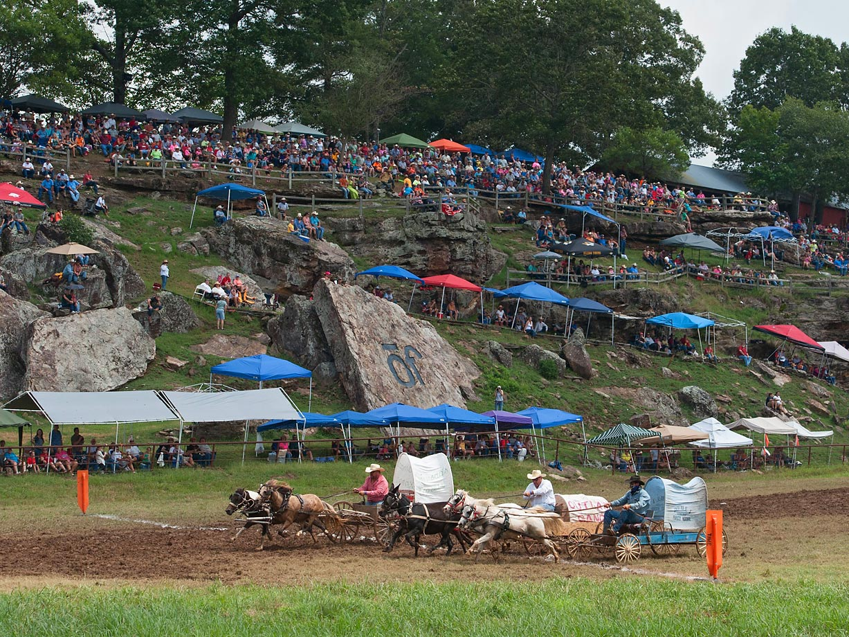 "Team ""Crossroads Express"" nudges team ""Outlaw Gang"" and team ""Double J"" at the finish line as the crowd looks on during the Oklahoma Land Rush."