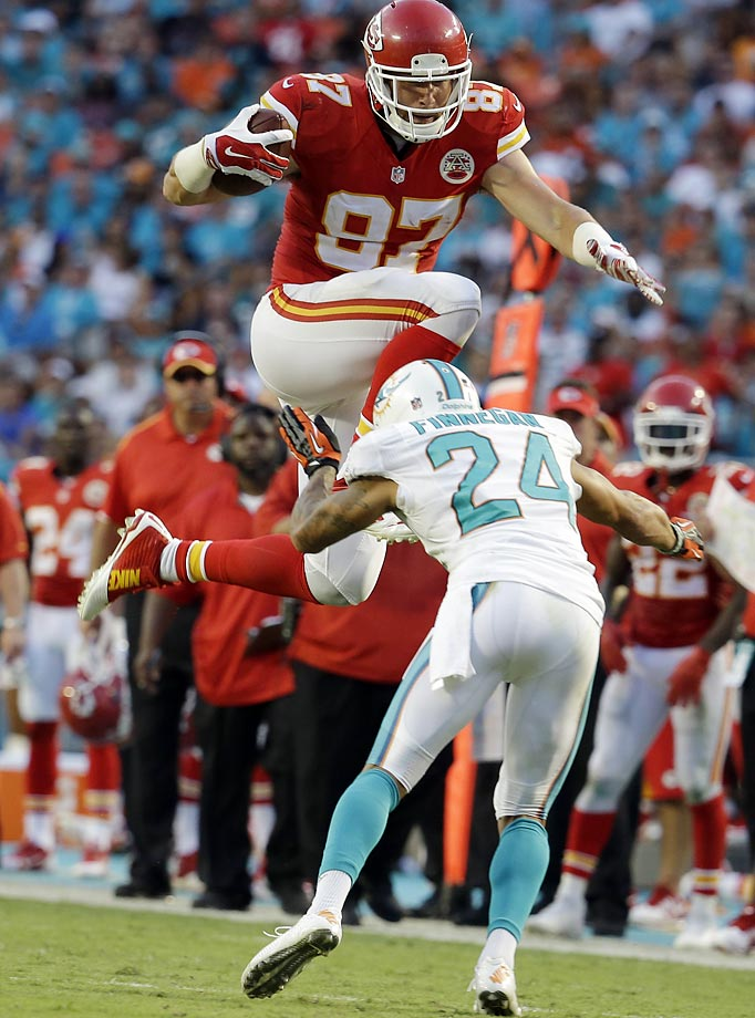 Kansas City Chiefs tight end Travis Kelce jumps to avoid a tackle by Miami Dolphins cornerback Cortland Finnegan.