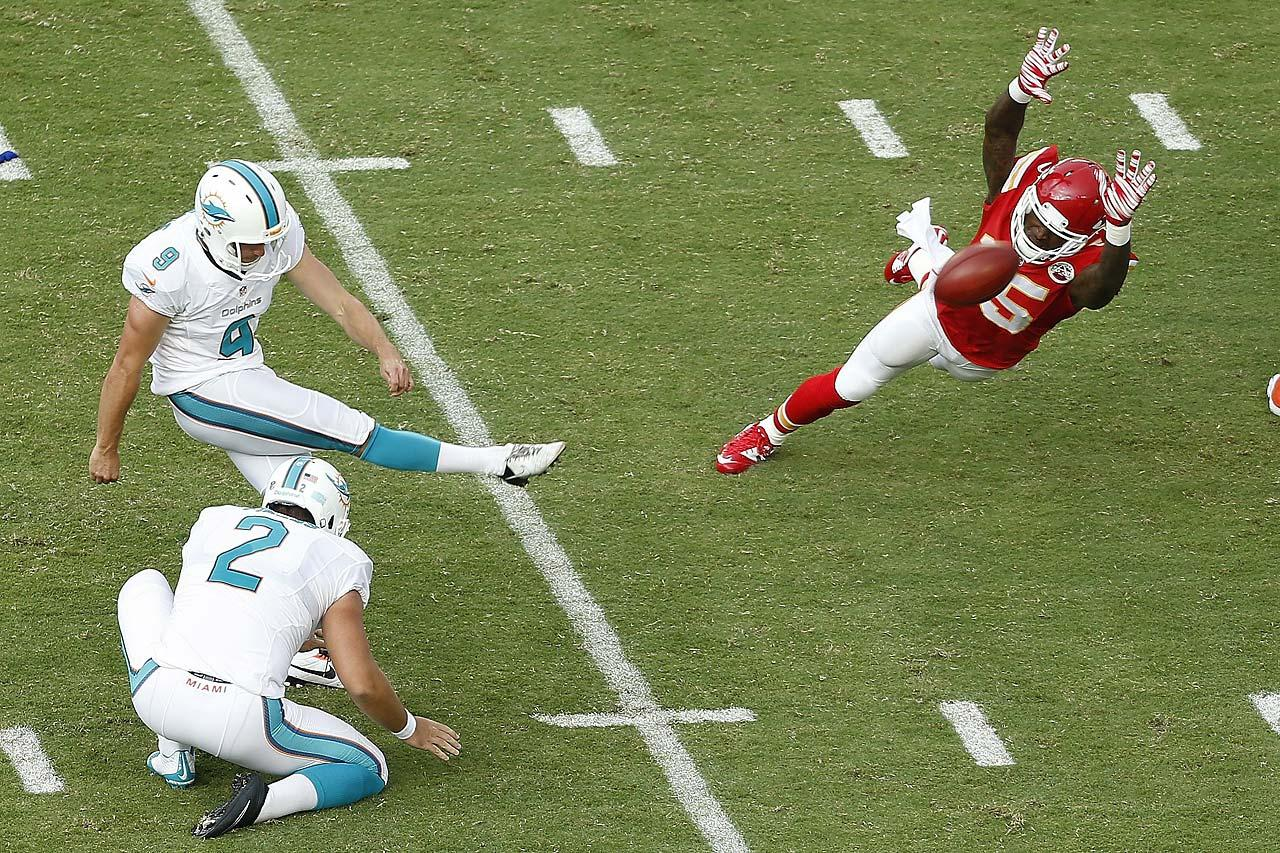 Caleb Sturgis of the Miami Dolphins kicks a third-quarter field goal as A.J. Jenkins of the Kansas City Chiefs unsuccessfully defends.