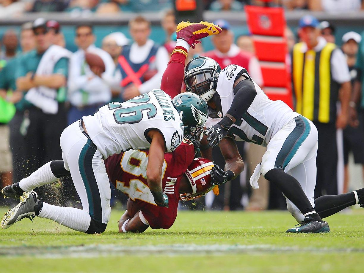 Redskins tight end Niles Paul is brought down by Eagles defensive backs Cary Williams and Malcolm Jenkins.
