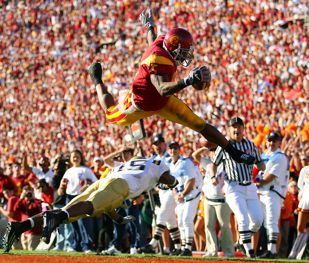 USC vs. UCLA, Dec. 3, 2005 | USC running back Reggie Bush jump over UCLA defender Marcus Cassel and into the end zone for a touchdown. Bush's spectacular season earned him the 2005 Heisman Trophy, but the award was later stripped because Bush had received illegal benefits during his time with the Trojans.