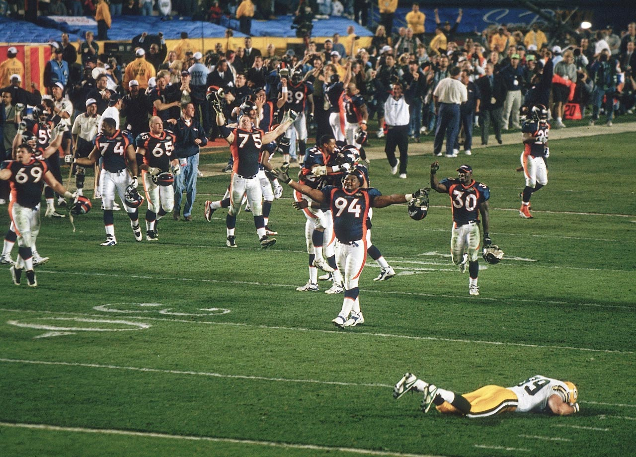 Keith Traylor, Terrell Davis and the Denver Broncos celebrate while Green Bay Packers tight end Mark Chmura lies faced-down on the field after the Broncos' 31-24 victory over the Packers. Denver's win was the first Super Bowl title for the franchise and snapped a 13-game losing streak for AFC teams in the Super Bowl.