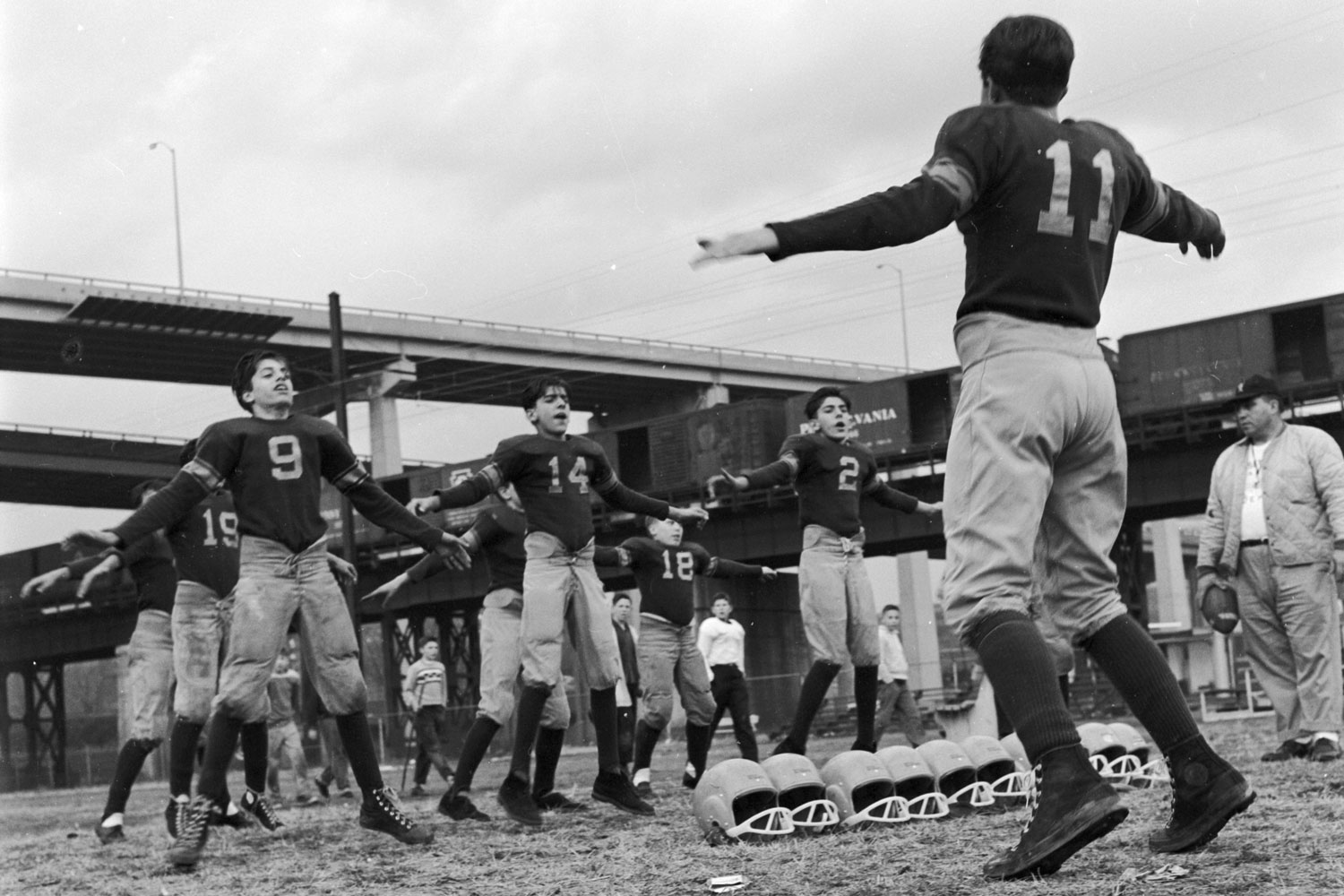 An American football team warms up before practice with some good 'ol jumping jacks in the late 1960's