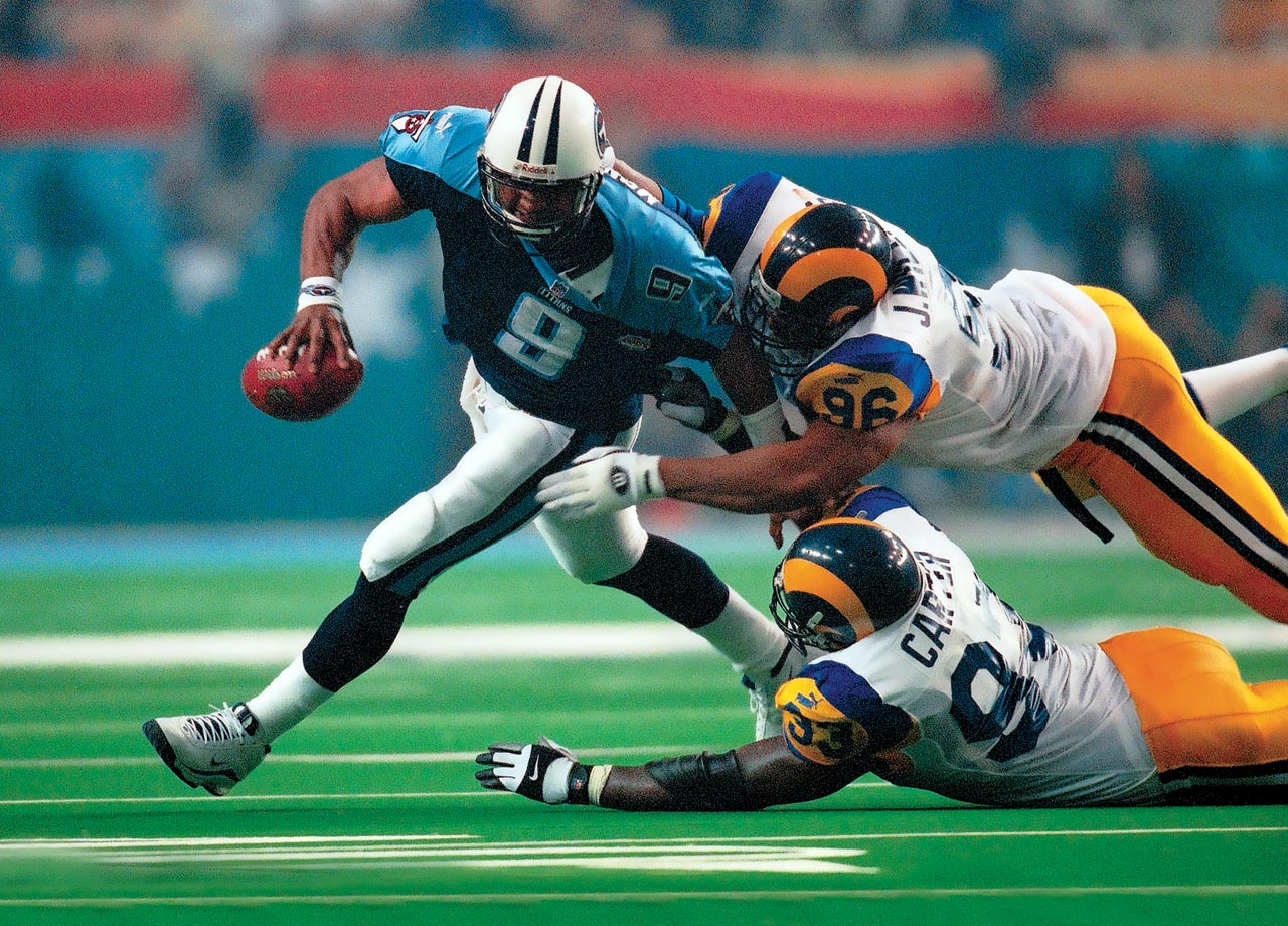 Tennessee Titans quarterback Steve McNair manages to avoid a sack and escape the tackles of the St. Louis Rams' Jay Williams and Kevin Carter during the final minute of St. Louis' 23-16 win. McNair threw for 214 yards and rushed for 64 more.