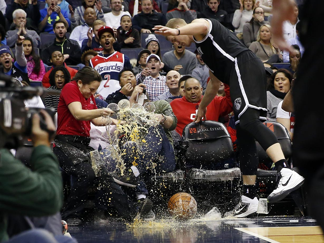 Waitress Deila Barr looses a tray of beers as Brooklyn Nets center Mason Plumlee runs into her chasing the ball in a game against the Washington Wizards.