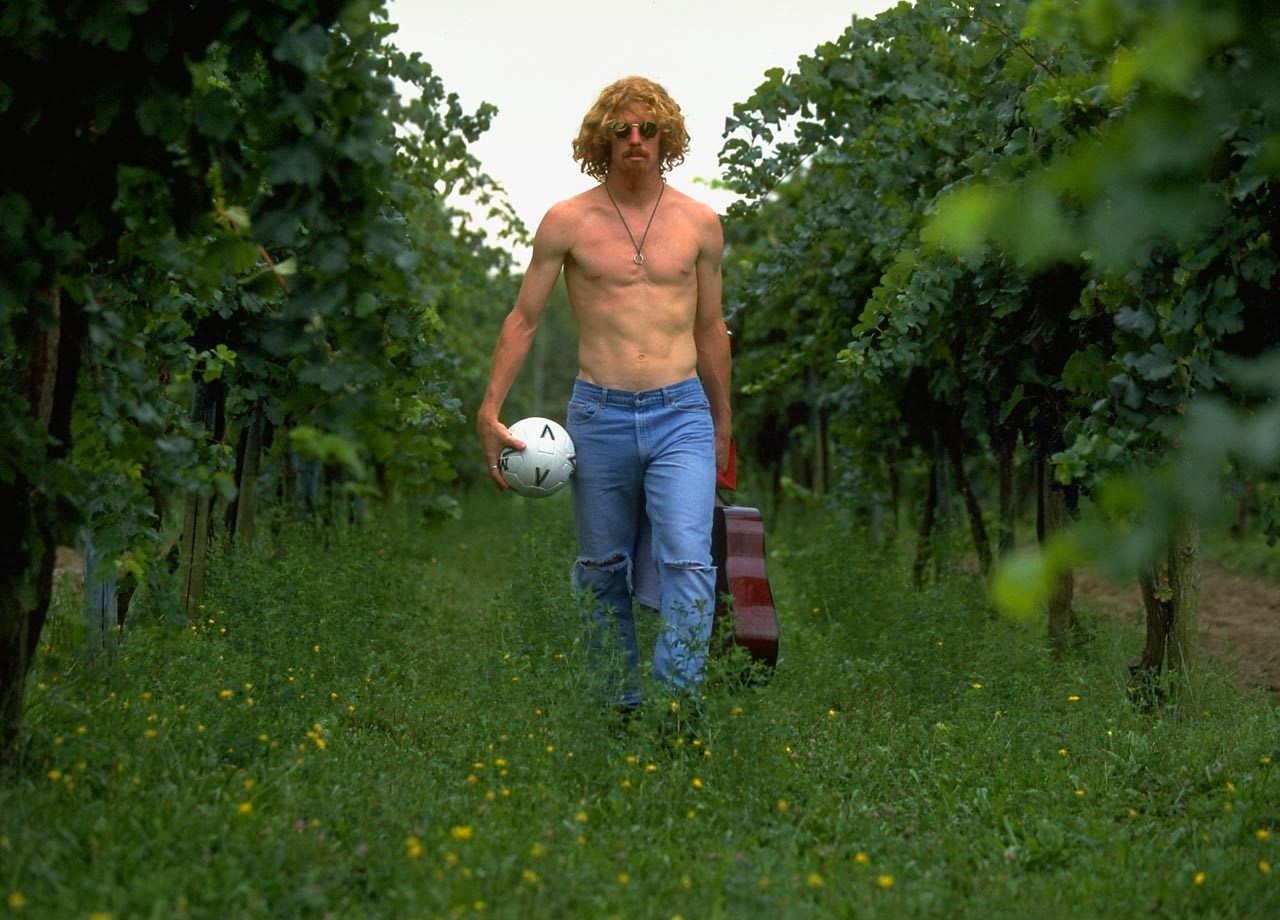 Fresh off an appearance with U.S. national team in the 1994 FIFA World Cup, Alexi Lalas strolls through a vineyard with a guitar and soccer ball.