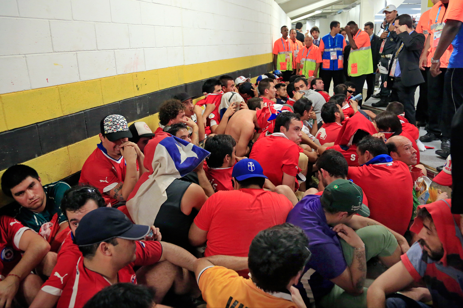 Chilean fans are surrounded by security personnel after breaking into Maracana Stadium before the group B World Cup soccer match between Spain and Chile