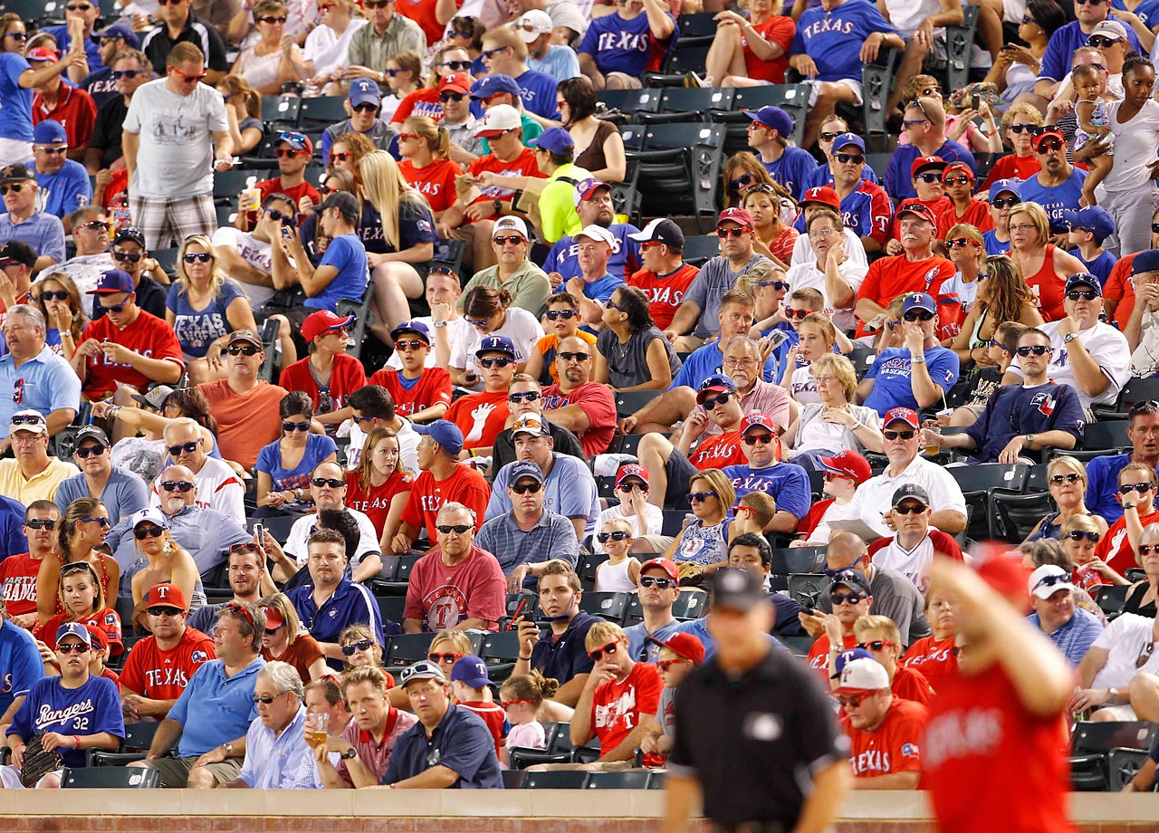 Texas Ranger fans wear sunglasses during the 7th inning of a night game against the Houston Astros at Rangers Ballpark in Arlington.