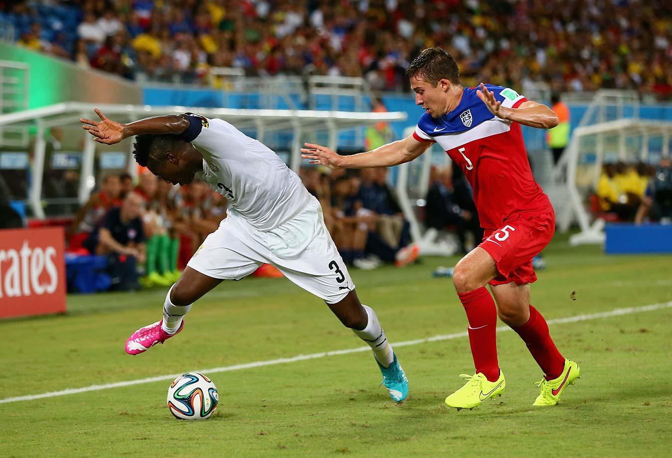 Asamoah Gyan of Ghana and Matt Besler of the United States battle for the ball.