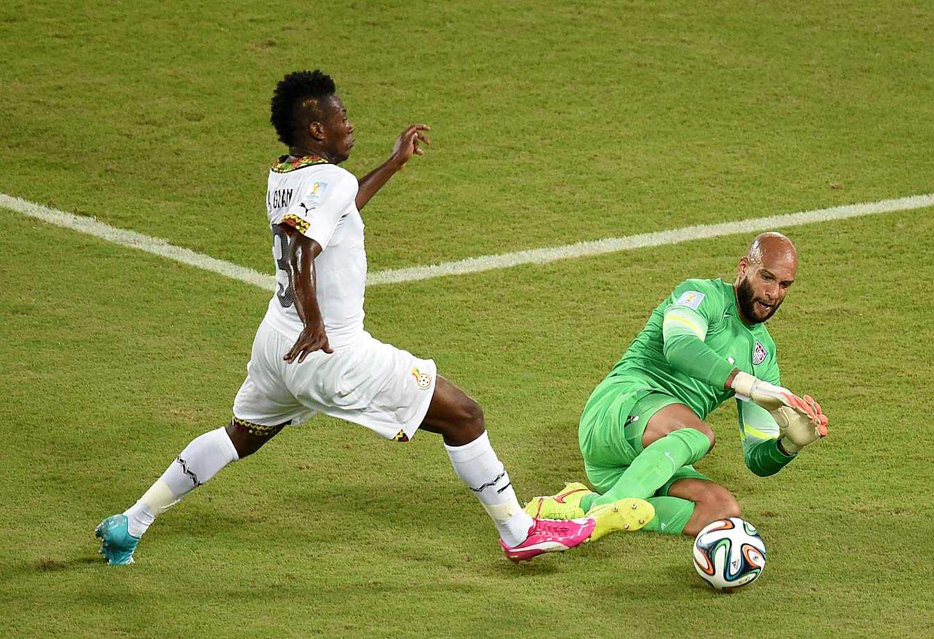 Ghana's forward Asamoah Gyan  vies with Tim Howard.