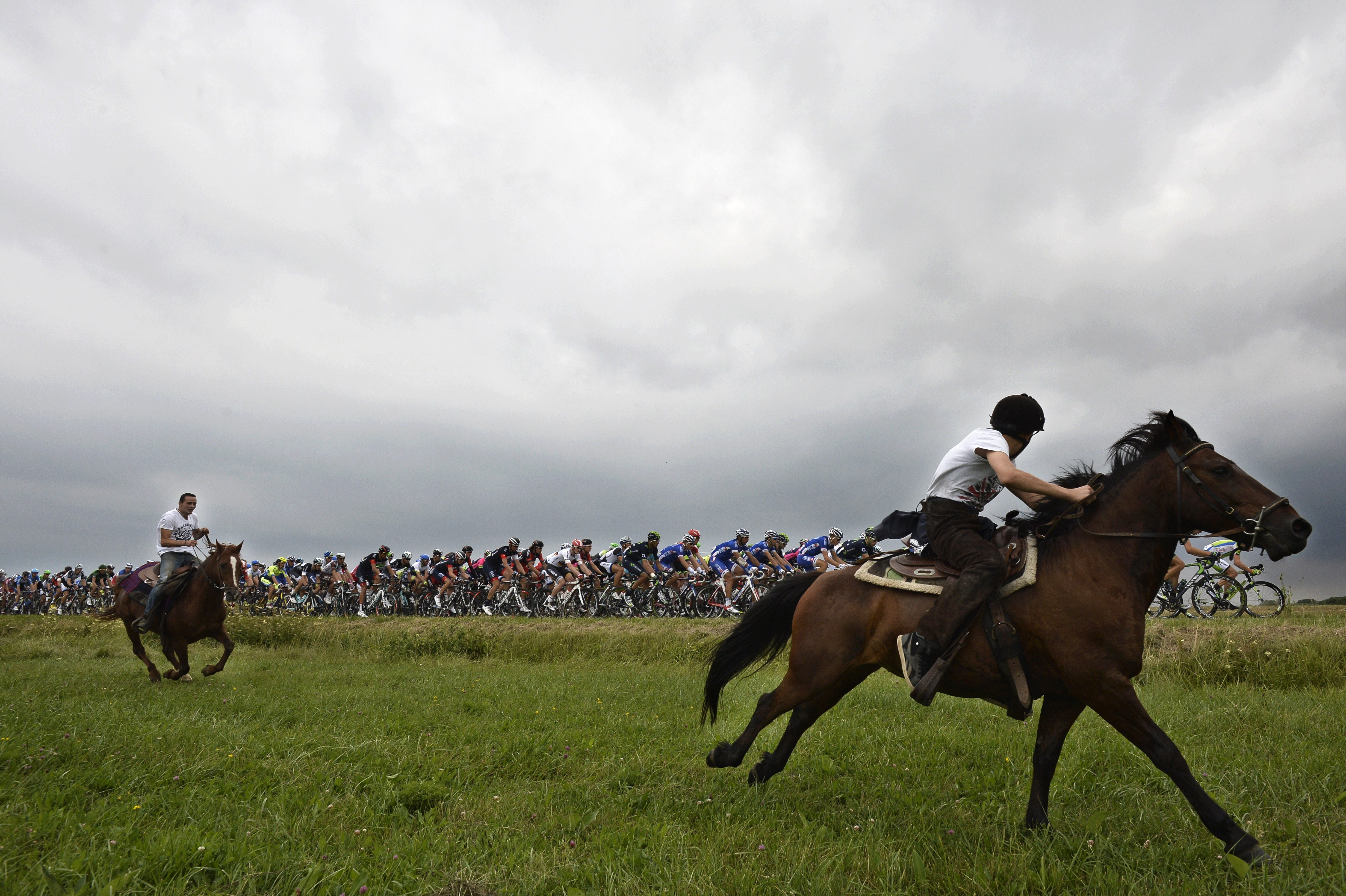 Horse riders are pictured as the pack rides behind during the 234.5 km seventh stage.