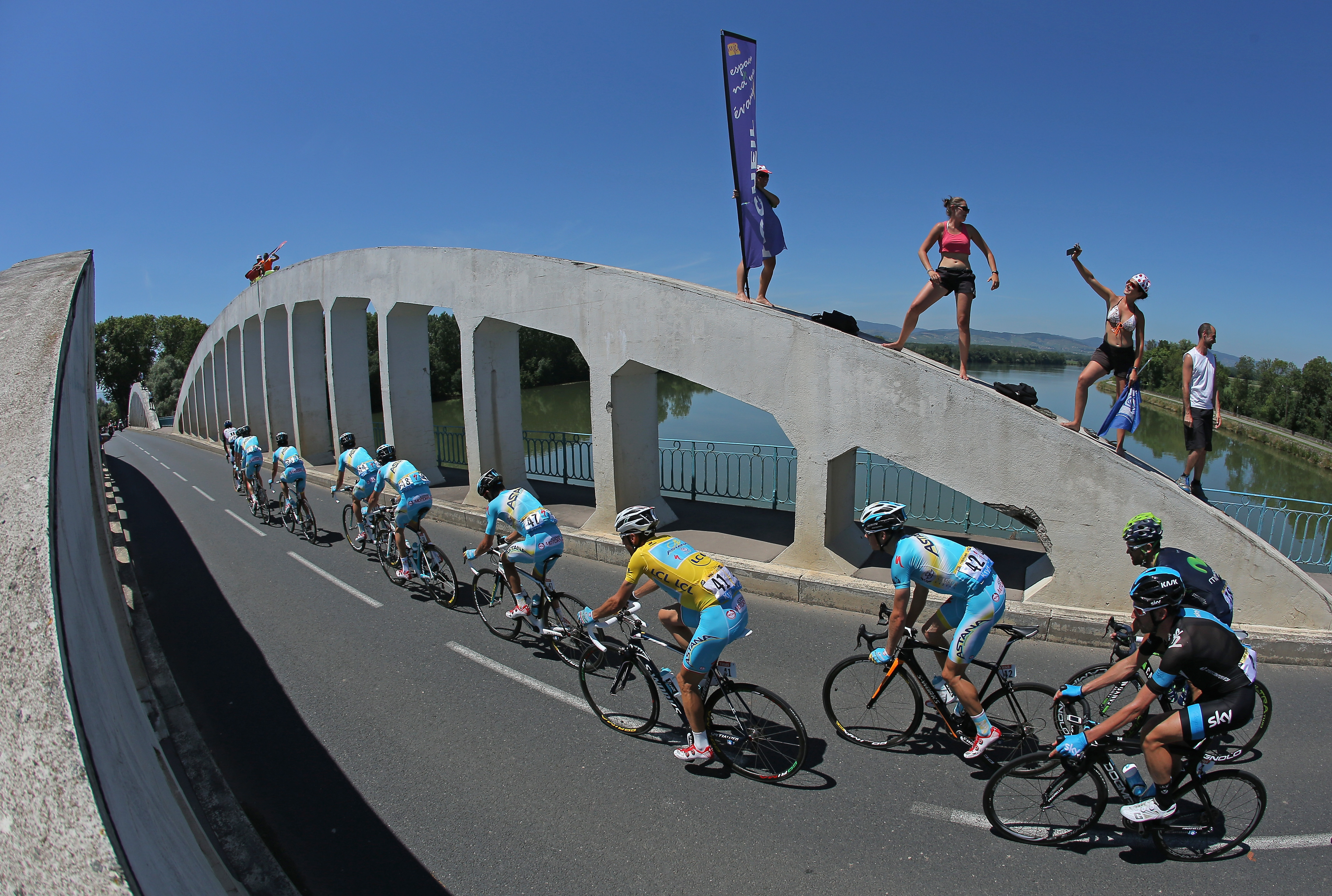 Vincenzo Nibali of Italy and the Astana Pro Team in the overall race leader's yellow jersey follows his team in the peloton over La Saone River during the twelfth stage.