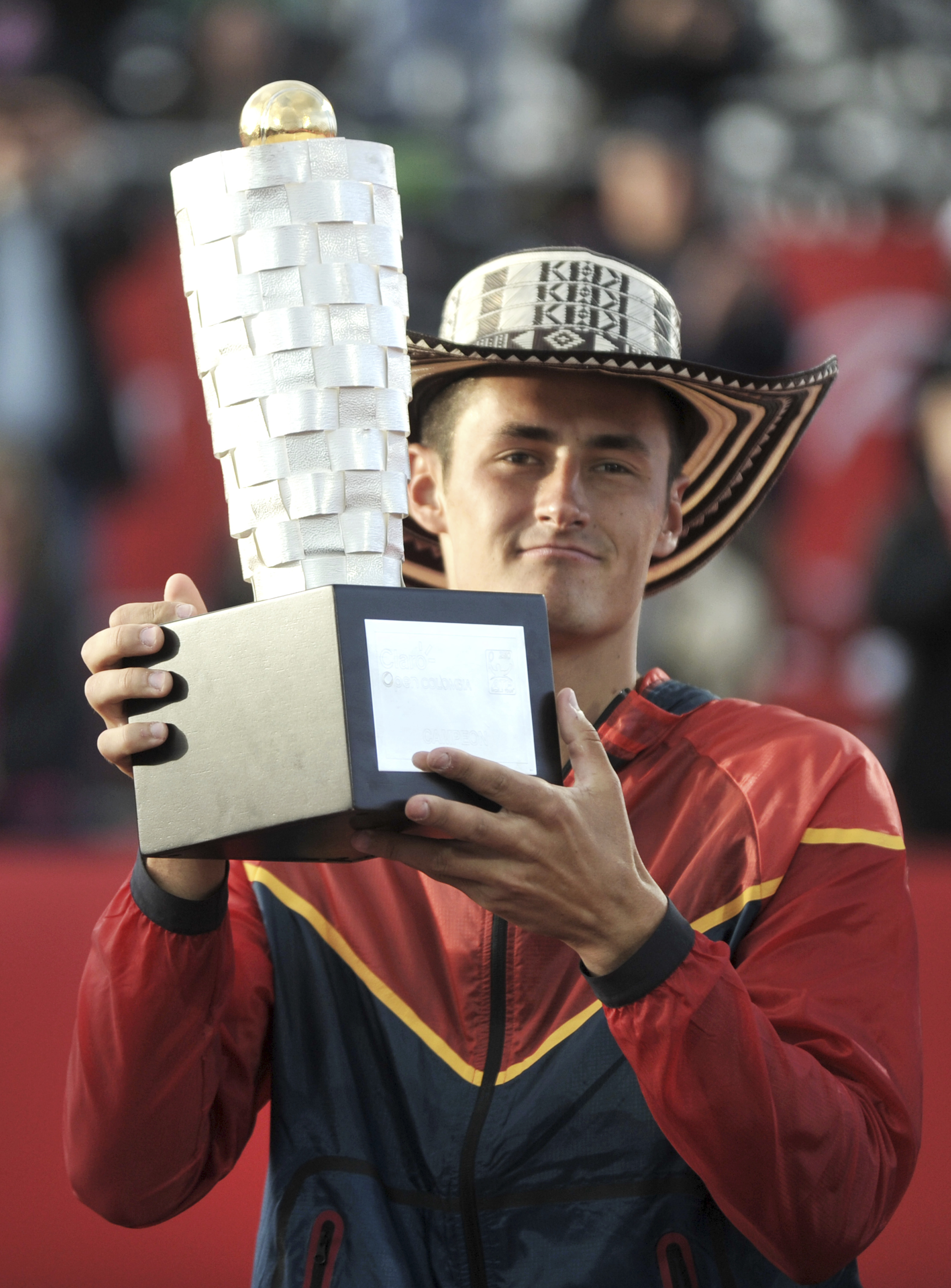 Tomic gets a hat and a trophy after winning the Copa Claro Open.