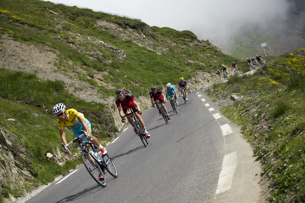 Nibali wearing the overall leader's yellow jersey rides in the pack.