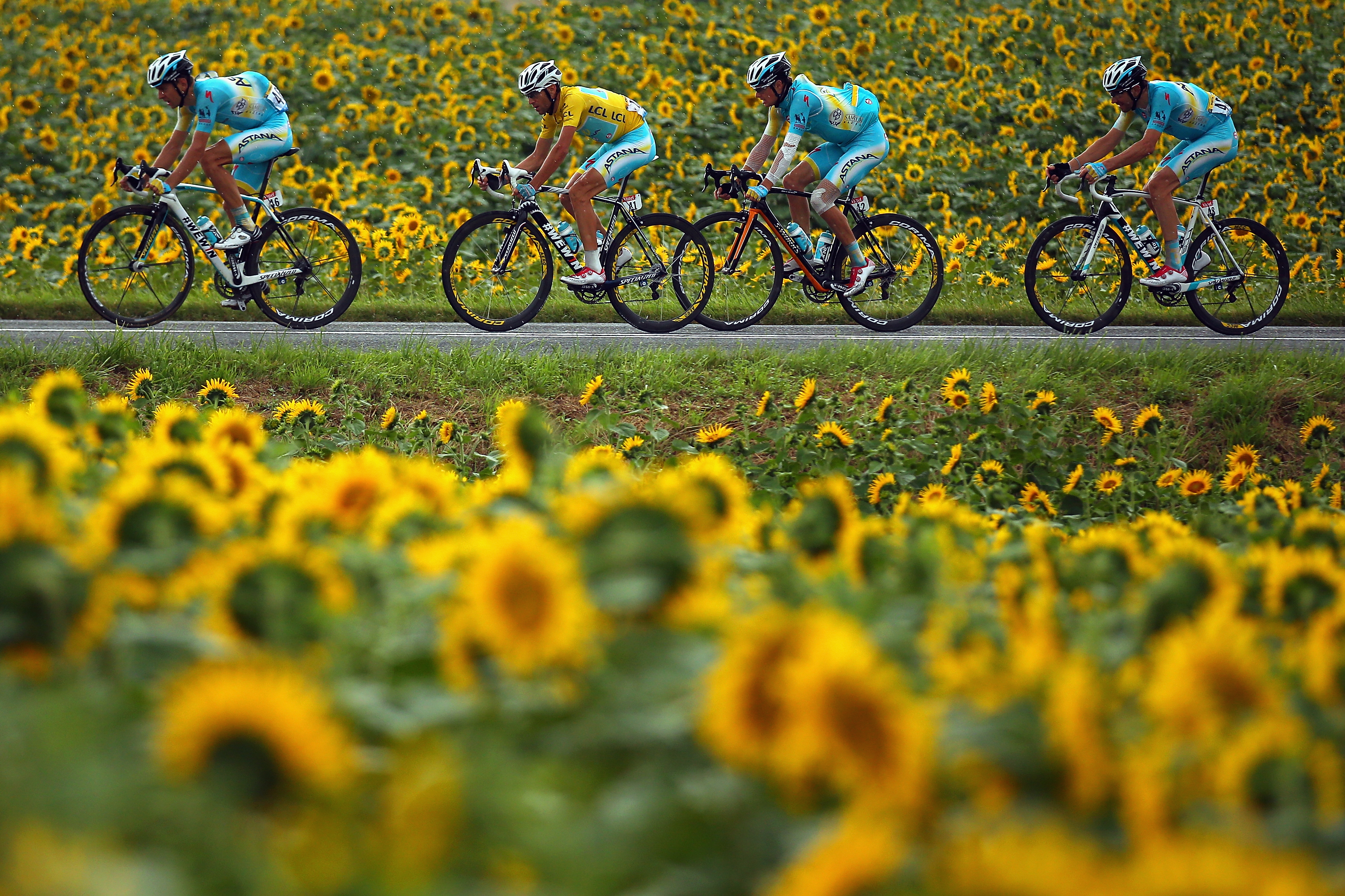 The race leader and yellow jersey Vincenzo Nibali of Italy and Astana Pro Team rides flankled by his teammates during the nineteenth stage of the 2014 Tour de France.