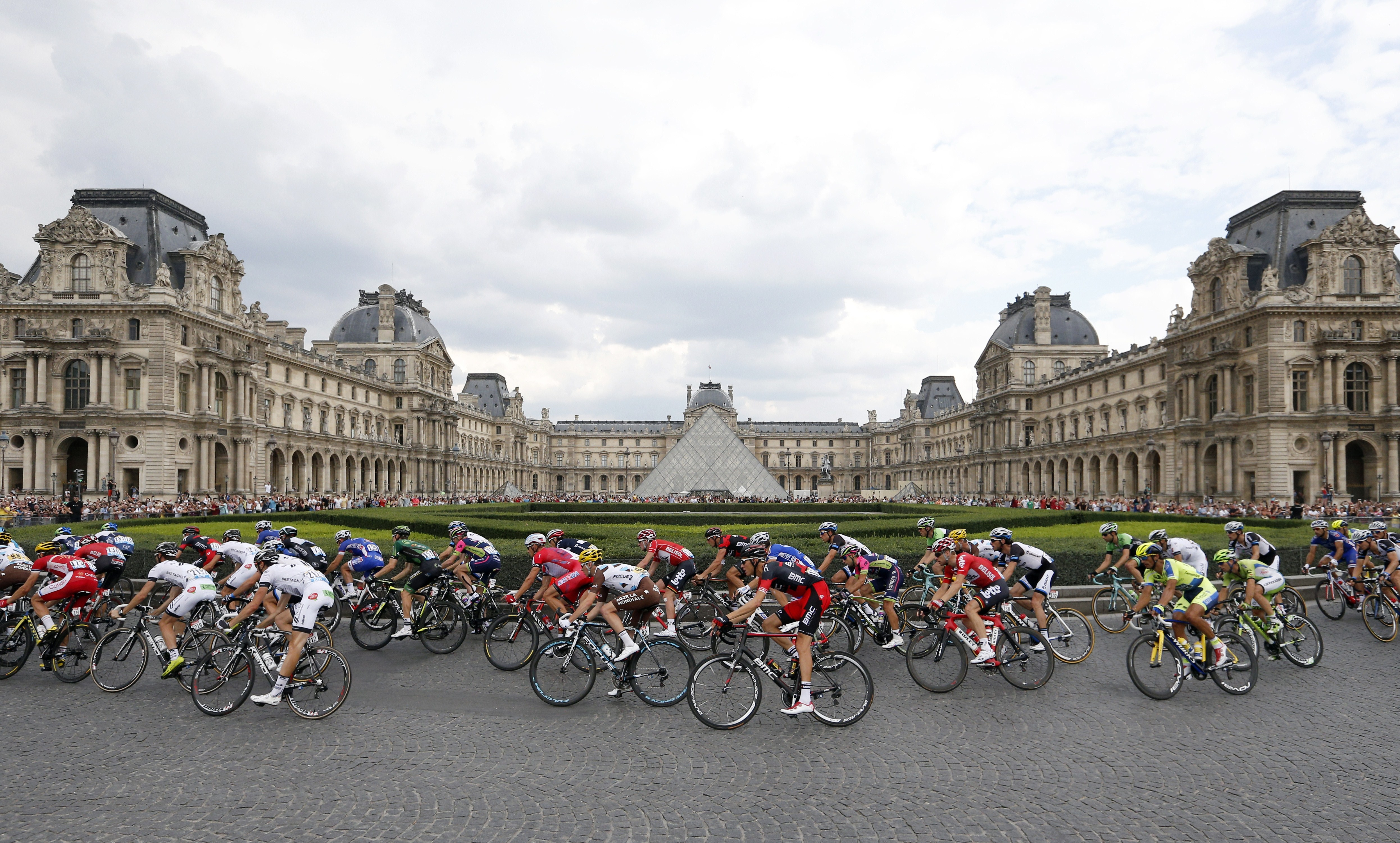 The pack rides past the Louvre Pyramid in Paris during the 137.5 km twenty-first and last stage.