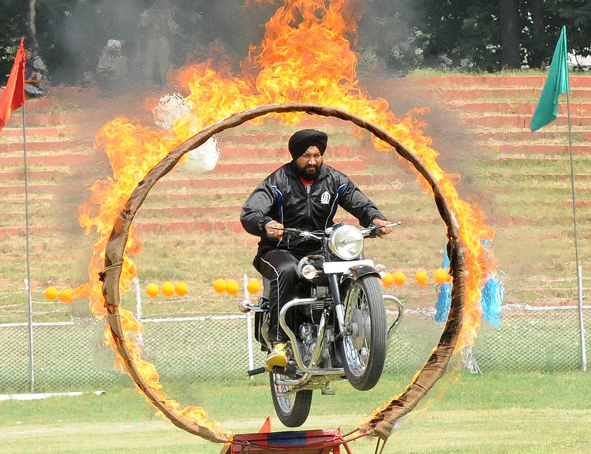 A motorcyclist drives through a fire ring during celebrations of India's 68th Independence Day at The Bakshi Stadium in Srinagar.
