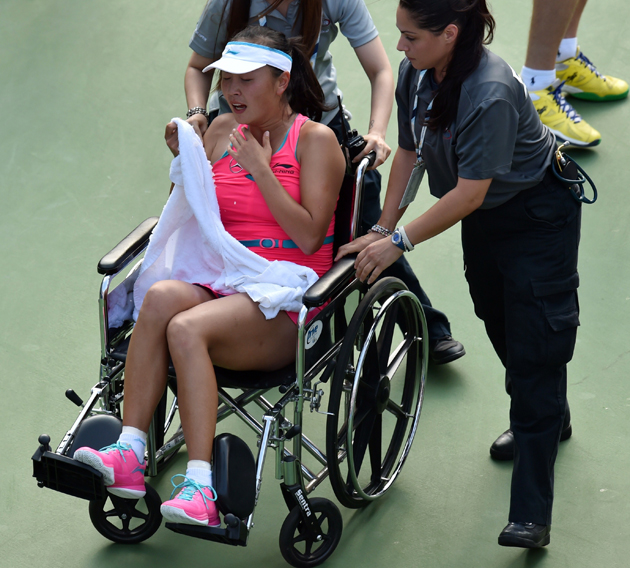Peng is taken from the court in a wheelchair after an injury during her semifinal match on Friday afternoon.