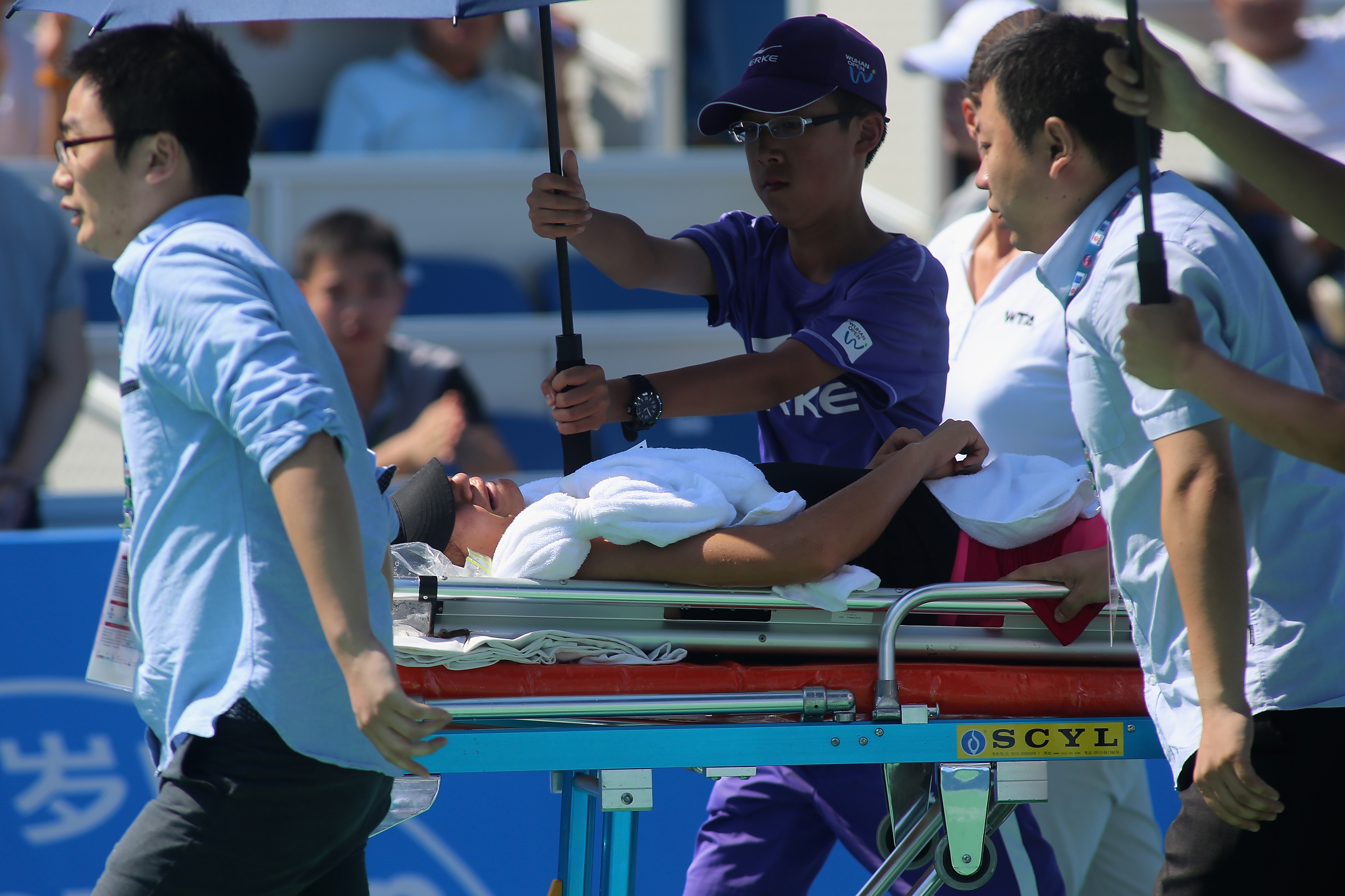 Shilin Xu of China lays on stretcher after injured during her match against American Alison Riske.