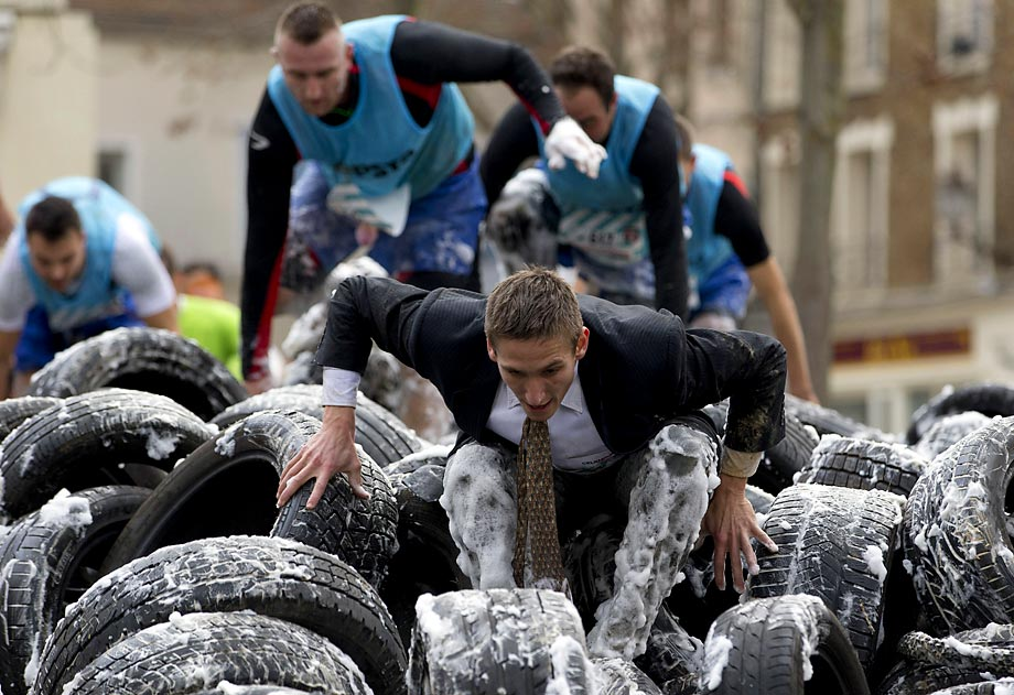 "Participants covered in foam climb over tires during the ""Fishermans Friend StrongmanRun"", a 24-kilometre obstacle course in Paris."
