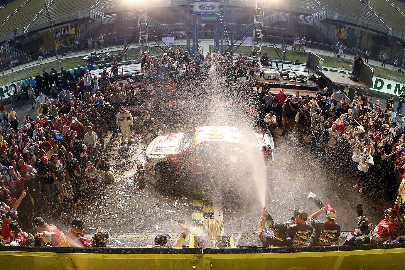 Kevin Harvick celebrates with champagne in victory lane after winning the NASCAR Sprint Cup Series Ford EcoBoost 400 at Homestead-Miami Speedway, his fifth checkered flag of the 2014.