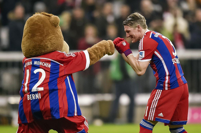 Mayern Munich's Bastian Schweinsteiger jokes with mascot Berni.