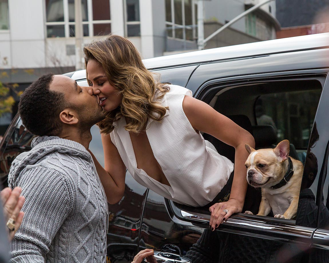 Sports Illustrated Swimsuit model Chrissy Teigen leans out to kiss John Legend during a photo shoot in the East Village.