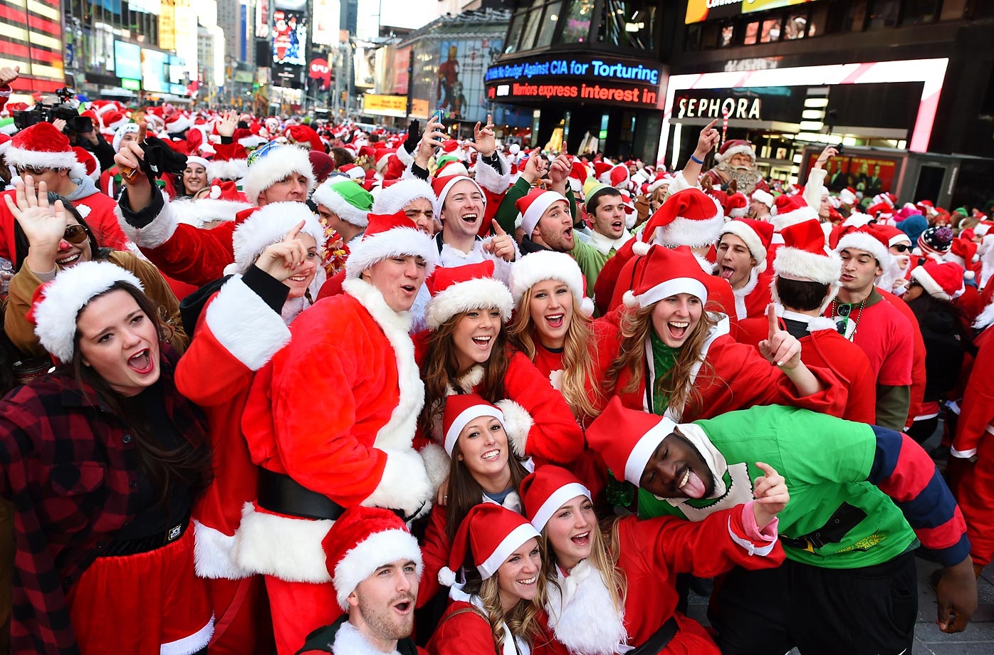 Santa Claus and Mrs. Claus pose in Times Square as they gather for the annual Santacon festivities.