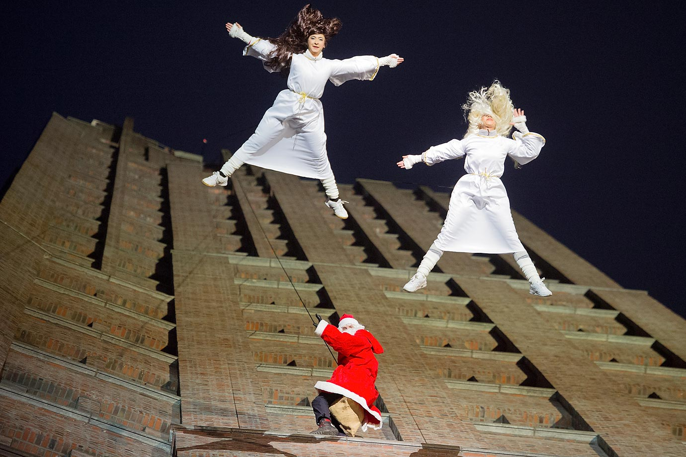 Climbers dressed as Santa Claus and two angels perform in an acrobatic dance show on the Kollhoff Tower in Berlin.