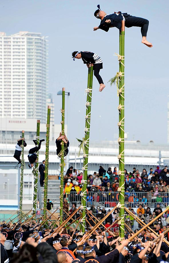Members of the Edo Firemanship Preservation Association balance on top of bamboo ladders as they perform ladder stunts during the New Year's fire review conducted by the Tokyo Fire Department.