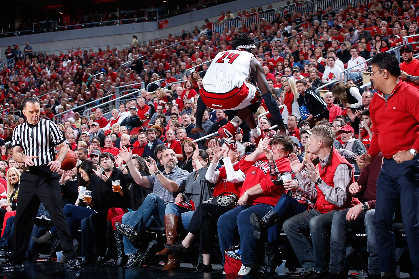 Montrezl Harrell of the Louisville Cardinals jumps over a section of fans while trying to save the ball from going out of bounds during a game against North Carolina State.