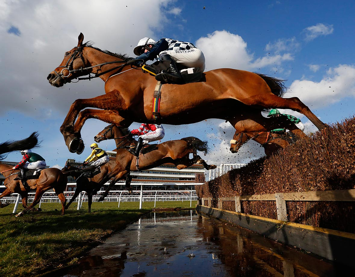 A general view as runners clear the water jump in The Agetur UK Novices' Limited Handicap Chase at Newbury racecourse.